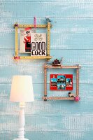 Square frames made from folding rulers fixed with cords hanging on sky blue wooden wall