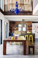 Solid wooden table and matching bench on concrete floor in front of kitchen area with yellow bar stools below mezzanine in open-plan interior