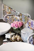 Detail of washstand with designer, wall-mounted taps and tiles in various Oriental patterns