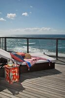 Comfortable sun lounger with cushions and painted side table on wooden deck; view of ocean over balustrade