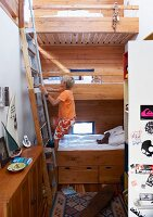 Boy climbing ladder in front of bunk beds in narrow, high-ceilinged children's bedroom