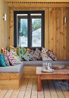 Comfortable corner bench with various cushions and coffee table in wood-clad loggia