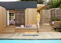 Patterned floor cushions on wooden deck next to pool and bench with various cushions outside wooden house