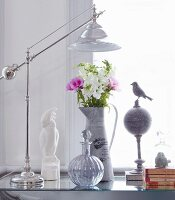 Table lamp with shiny chrome frame, spherical bottle with stopper and bouquet in zinc jug on glass table top