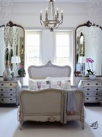 French-style bedroom - bed with curved wooden frame below window flanked by mirrors and glass pendants hanging from ceiling
