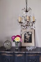 Chandelier with glass pendants above alarm clock and posy of roses of vintage bedside cabinet