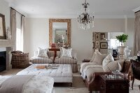 Elegant sofas around ottoman in traditional living room with chandelier and gilt-framed mirror