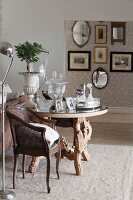 Antique, cane-backed armchair next to round table with carved legs, antique collectors' items in background and gallery of pictures in background in elegant interior