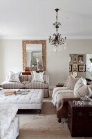 Sofa set around ottoman and chandelier with glass pendants in elegant living room in shades of pastel beige