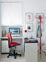 Home office integrated in niche with tall cupboard, drawer unit on castors and sideboard to one side used as partition
