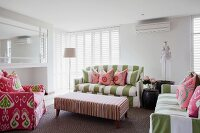 Green and white striped sofa and armchair with ikat pattern around ottoman in white interior