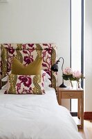 Plain and patterned scatter cushions against bed headboard with matching upholstery; retro table lamp on bedside table