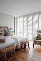 Rustic wooden benches at feet of twin beds in bedroom with white, interior shutters on glass wall