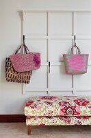 Shopping bags hanging on white cloakroom rack above floral ottoman