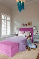 Teenager's bedroom in shades of lilac with blue feather boa draped on chandelier; girl and dog sitting on floor