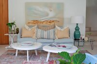Two coffee tables with white, amorphous tops and pale blue sofa below landscape on wall