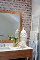 Simple wooden washstand with white stone counter and framed mirror on exposed brick wall; white ladder used as towel rack