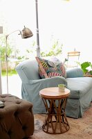 Round, ethnic side table next to pale grey couch and retro standard lamp; garden view