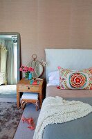 Colourful, ethnic scatter cushion on bed and solid wood bedside table against wall