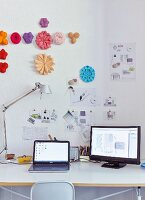 Laptop with additional monitor on desk next to Tolomeo table lamp in front of work models and drawings pinned to wall