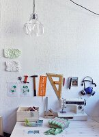 Sewing machine and accessories on desk below drawing utensils, rulers and templates hung on wall