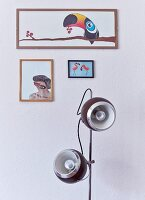 Restored standard lamp below framed, artistic pictures on wall