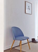 Blue, fifties chair against white wall in simple, white hallway