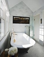 Bathroom with free-standing vintage bathtub below window in attic bathroom with white and grey wallpaper