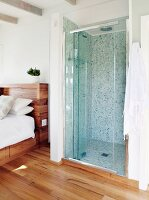 Shower with mosaic tiles and glass partition integrated into simple bedroom with parquet floor