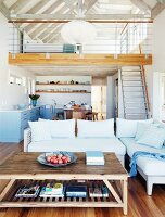 Open-plan living area with mezzanine and exposed roof beams in modern holiday home