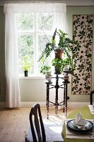Various foliage plants on flower stand made from turned wood below window next to panel with botanical pattern