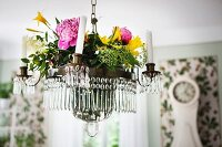 Summer flowers on chandelier with glass droplets and white candles suspended from ceiling