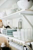 Glasses and crockery on white bracket shelves