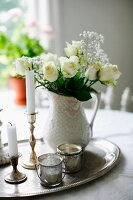 White roses and gypsophila in china vase next to candlesticks & tealight holders on silver tray; vintage arrangement