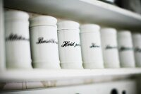 Labelled, white china spice jars on shelf