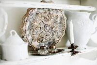 Vintage, ornamental plate between sugar bowl and white, chine jug on shelf