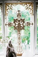 Ornate crucifix made from white-painted metal in front of window