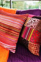 Colourful scatter cushions in various shades of red with Oriental-style striped and patchwork covers on couch