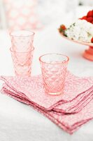 Pink, retro drinking glasses on pink and white patterned, vintage-style linen napkins