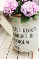 Purple hydrangeas in zinc bucket with lettering on rustic wooden terrace