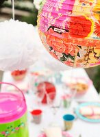 Floral print on lantern above table set in bright colours for garden party