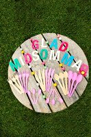 Plastic and wood cutlery in pastel shades and Swedish greeting made from colourful letters on garden table on lawn