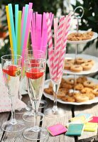 Champagne with strawberries in flutes on garden table; colourful straws and cake stand of biscuits in background