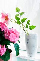 Pink flower in white glazed vase next to house plant with pink flowers