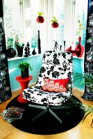 Swivel easy chair with black and white floral upholstery on round rug in corner; collection and black and red vases on windowsill