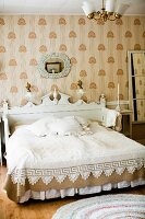 Double bed with white, carved headboard against wallpapered wall in traditional bedroom in shades of white and pale brown