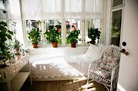 White rattan armchair and couch with lace blanket below window and potted plants on windowsills in loggia