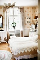 Bed with white lace bedspread in traditional bedroom in shades of white and beige