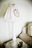 Table lamp with white-painted wooden base and fabric lampshade
