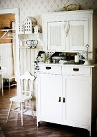 White-painted dresser and chair with carved backrest in traditional kitchen